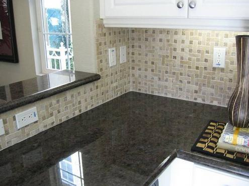 Basketweave backsplash. Would be even better if the switchplates were stone  to match the lighter