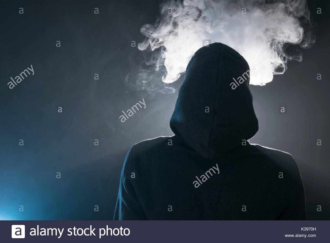 25465e74 Isolated young man smoking an electronic cigarette on a dark background,  holding a vaping device with lots of clouds. Stock Photo
