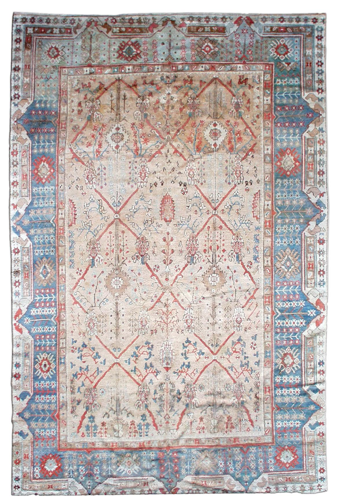 A late 19th century antique Turkish Ghiordes (Giordes) carpet, the camel field with vines forming an enlarged diamond lattice containing palmettes, flowering branches and scattered floral motifs within a sea blue flowerhead and raceme border. Circa 1880.