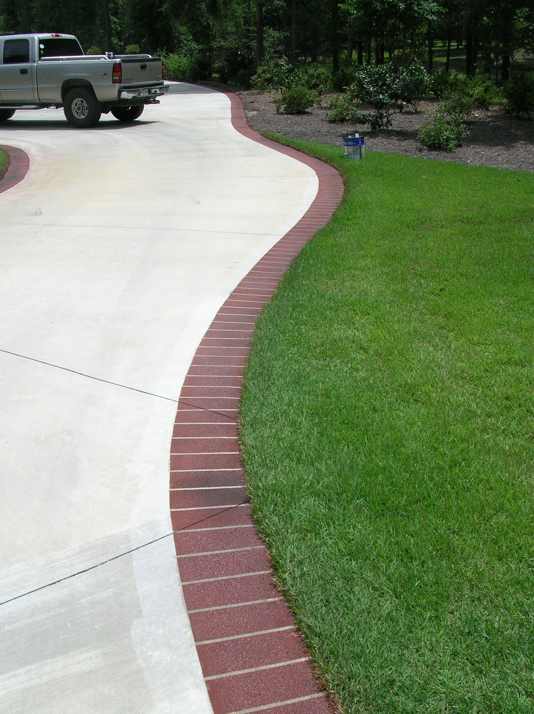 Brick edging for the driveway outdoor living spaces for Cement driveway ideas