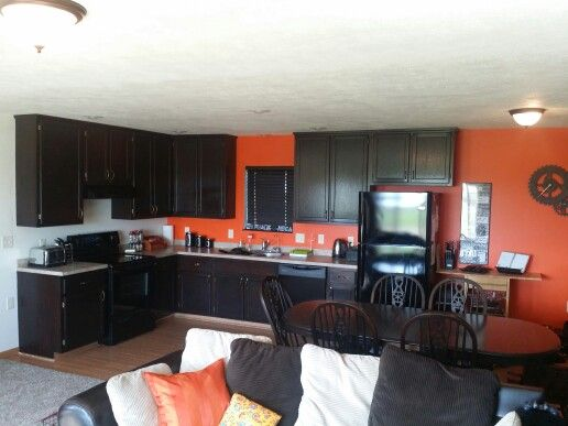 dark cabinets, orange wall , brown , burnt orange , kitchen