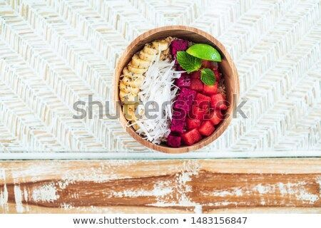 Photo: Fresh tasty smoothie bowl with dragon fruit, red watermelon, banana, coconut flakes and slice of lime. Healthy vegetarian natural breakfast. Wooden plate and background, top view.Stock Photo: Fresh tasty smoothie bowl with dragon fruit, red watermelon, banana, coconut flakes and slice of lime. Healthy vegetarian natural breakfast. Wooden plat...