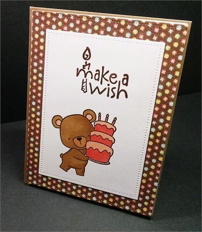 What a cute little birthday card for a little girl complete with a pink strawberry birthday cake being delivered by a brown teddy bear!   The card base is cut from brown kraft colored card stock. On the front, I layered it with a piece of paper with xs in different colored circles on a brown background. I die cut this into a rectangle using a die with a stitched edge. I cut another of the same size from Neenah white card stock and glued the two together.   I die cut a smaller stitched…