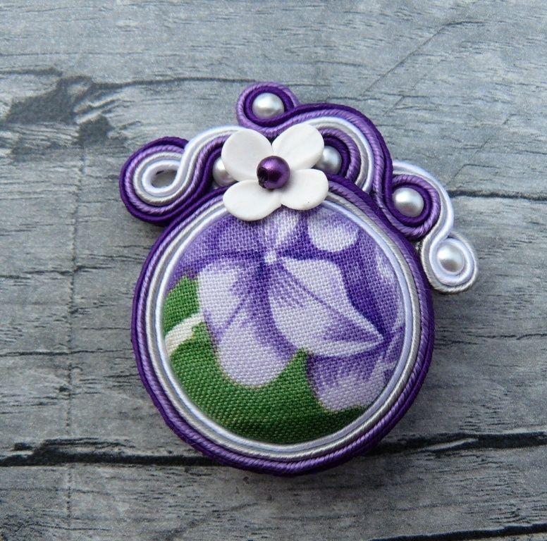S+květy+hortenzií+Brož+vytvořenáčasově+náročnou+technikousutaškování.+Brož+je+vytvořená+z+textilního+butonku+ve+fialové+a+zelené+barvě.Na+výrobu+byly+dále+použity+textilní+prýmky+-+sutašky+ve+dvou+odstínech+fialové+barvy+šedé+a+bílé+barvě,+voskové+perličky+ročně+vyráběný+polymerový+květ+od+LadyElik.+Velikost+brože+je+5x4,5+cm.+Brož+je...