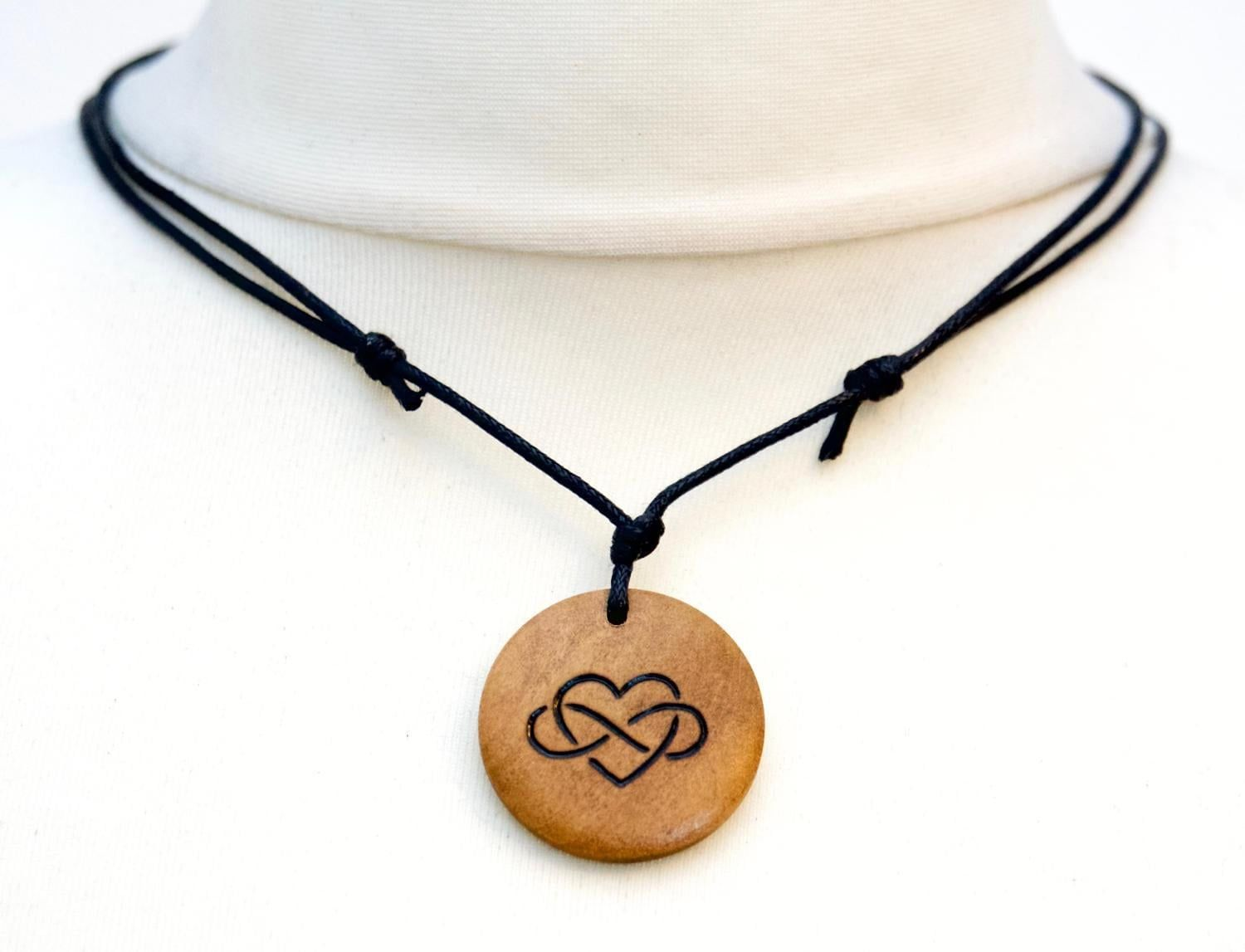 """""""Unique wooden necklace featuring a Polyamory or infinite love symbol. Handmade art jewellery that makes a unique and personal gift idea! Necklace Features: - Freehand wood burning, made to order - Unisex - 3cm diameter, 1.1/4\"""" - Adjustable slip knots on a black cotton cord: Can be worn as a choker to a low hanging pendant - No extra postage cost on multiple items from my shop Would you like to choose your own design? Check out my custom design listing or send me a message with your ideas!"""""""