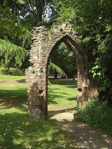 A stone garden arch resembling part of an old ruin makes an - mauerstein antik ockerbraun