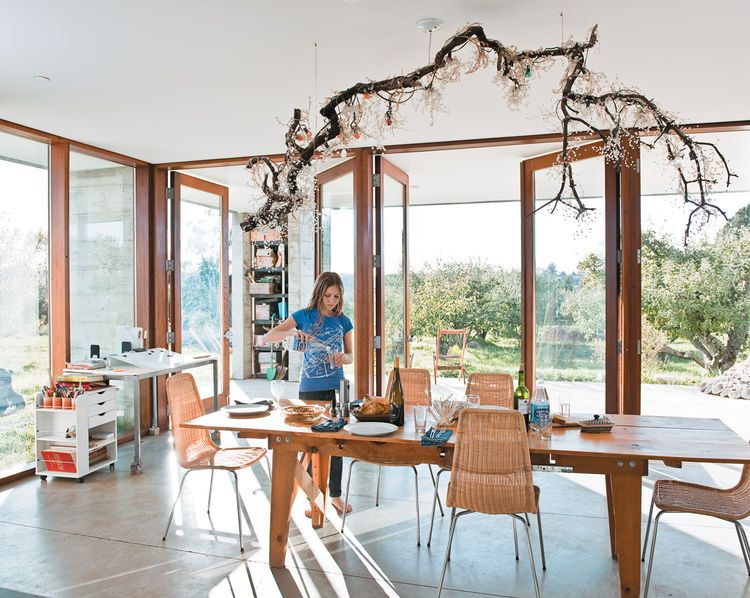 The dining room table sits at one end of the main room, with an open view onto the rows of trees that extend out from two sides of the house. Natasha sets the table underneath a suspended fixture made by her mother, Naomi, out of a salvaged branch, crysta