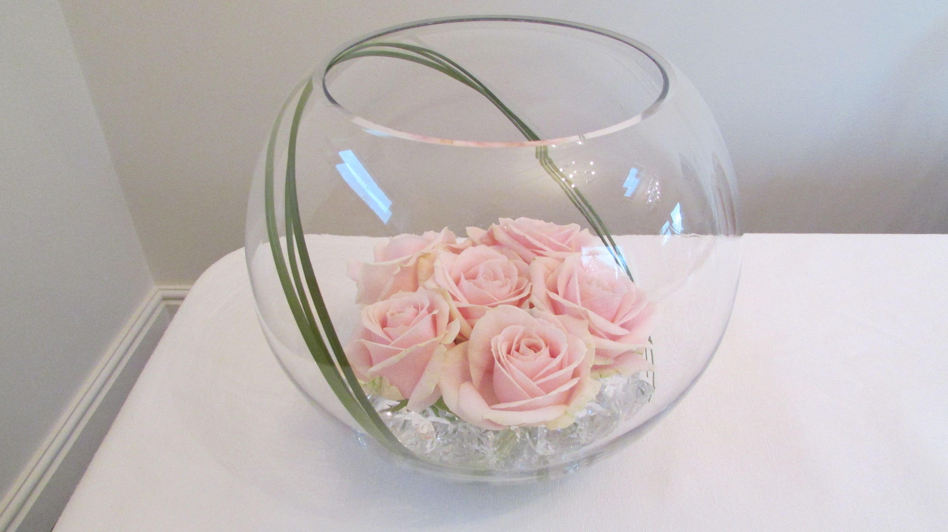 Large goldfish bowl with pink sweet avalanche roses ideal wedding table decoration, centrepiece