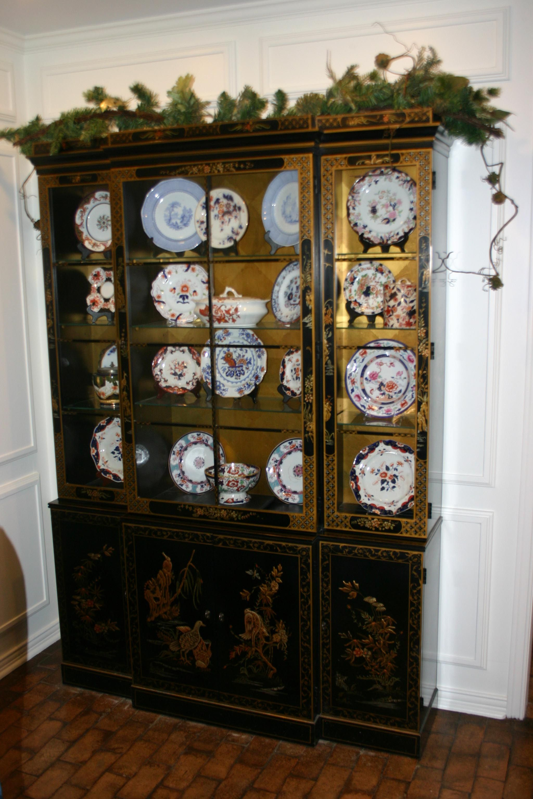 A garland decked with pine cones tops the Chinese lacquer cabinet