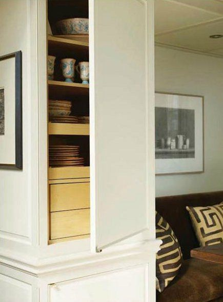 concealed storage comprised of cabinets built to look like an architectural niche in the room. Interior Design Ideas. Home Design Ideas