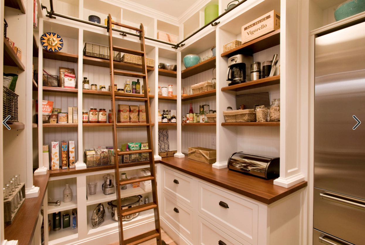 Pantry with wood counter tops, ladder to reach upper storage ...