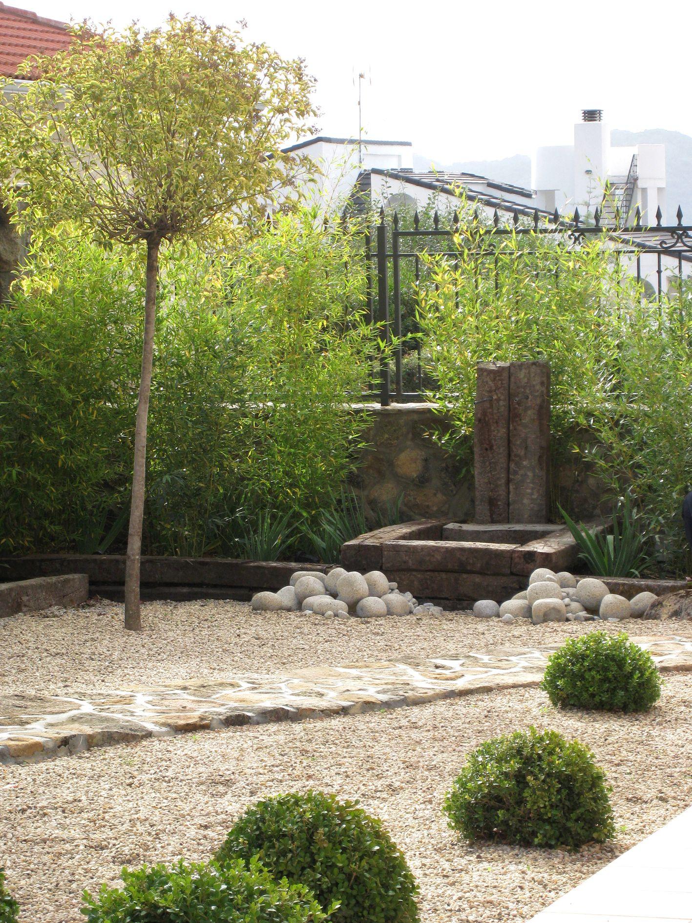 Sendero y suelo de piedra en jardín sostenible con fuente de ...