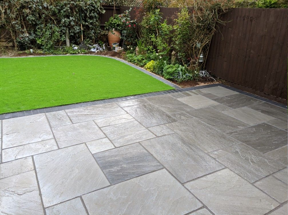 Natural stone patio with a artificial grass lawn completed