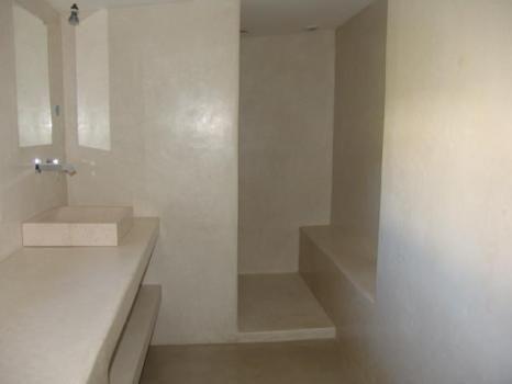 Clean white tadelakt sink and shower with bench tadelakt