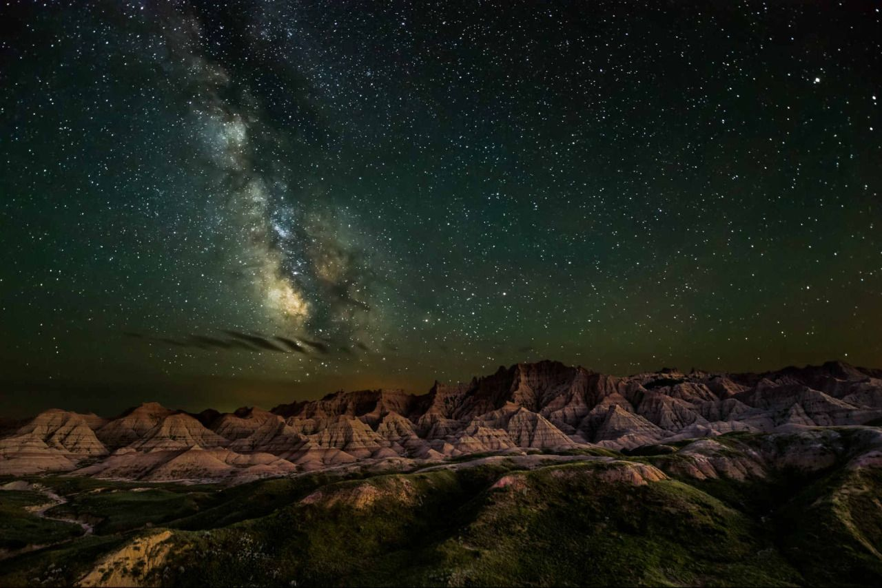 Bathed in starlight from the Milky Way, the unique rock formations of Badlands…