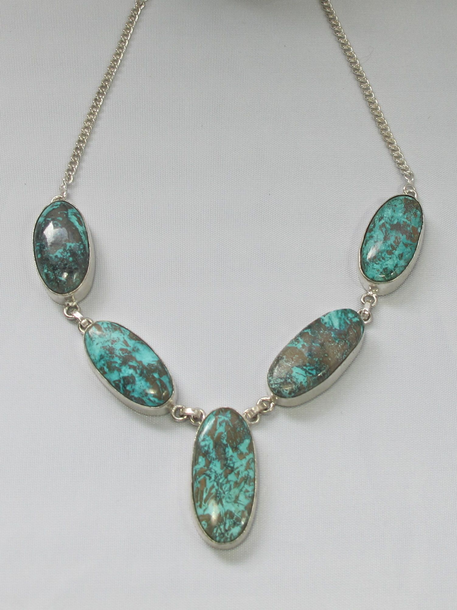 """Five intricate polished cabachon Chrysicolla gemstones adorn this necklace, set in 925 sterling silver and sterling overlay. Matching bracelet available separately. Length: 19"""" Lobster claw clasp. Lar"""