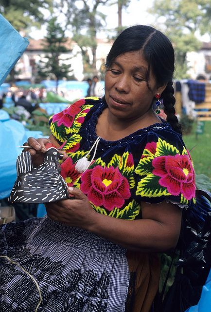 Thomas Aleto ~ A ceramic artist from Ocumicho Michoacan paints a figure of a chicken. Day of the Dead market. Patzcuaro, Michoacan, Mexico.