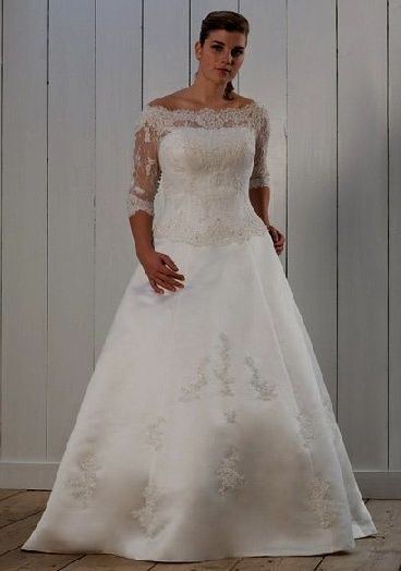 809fba0d958f Plus size wedding dress designs with an illusion neckline have a romantic  feel. This 3/4 sleeve wedding dress also features an a-line style ball gown  skirt.