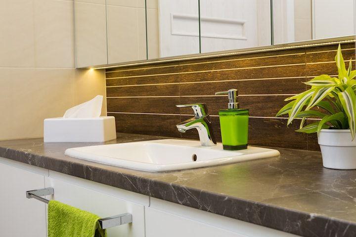 Kleine badkamer met led verlichting onder kast en groene