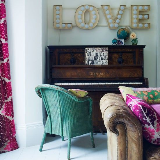 The old, vintage piano adds charm to this living room area, while the painted green armchair adds a pop of color.
