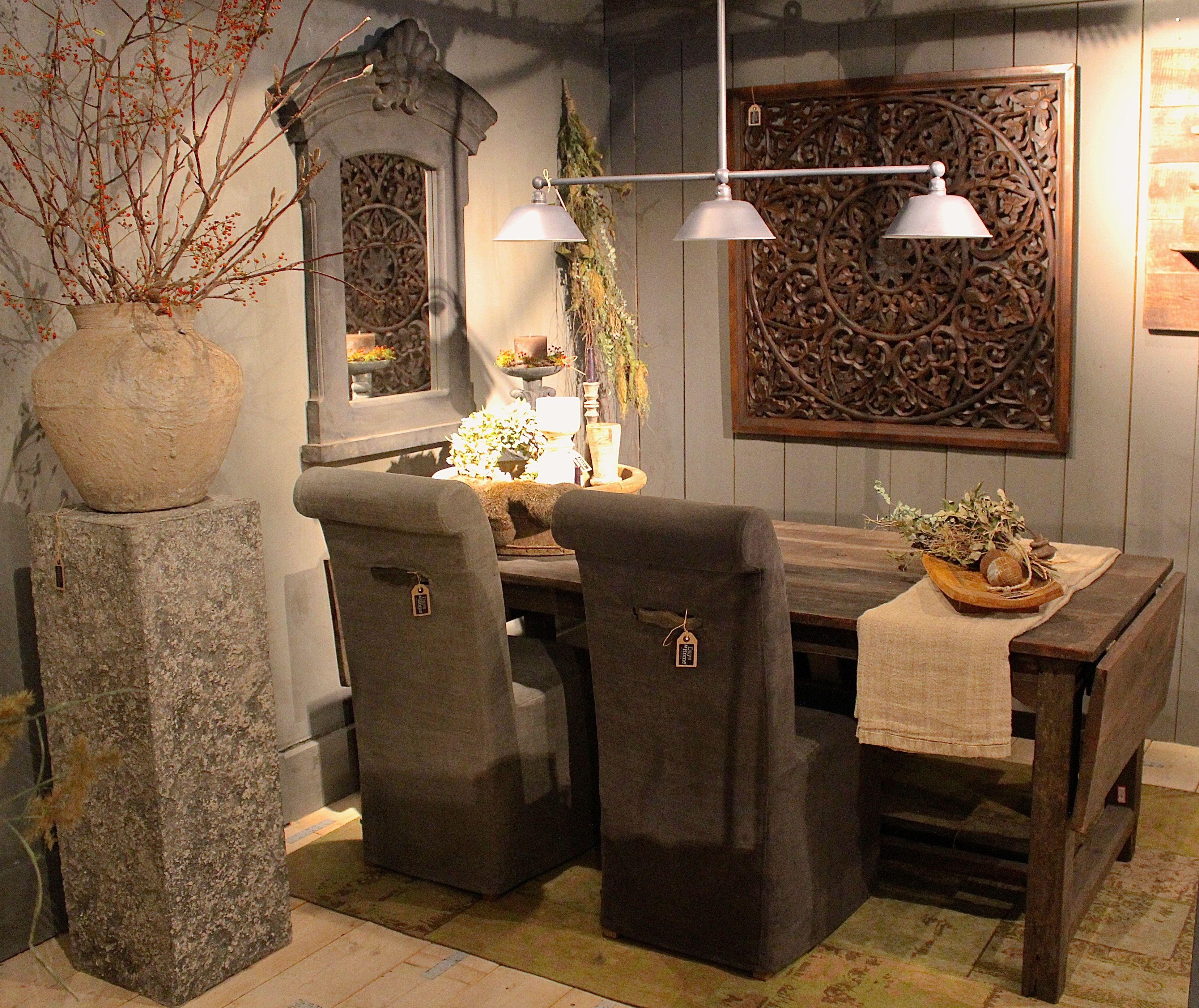 Eettafel en eetkamerstoelen, kruik en spiegel en groendecoratie ...