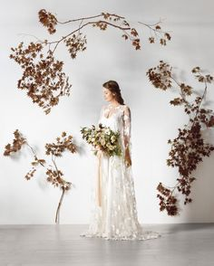 """""""Fall flowers can sometimes look heavy, but this ceremony marker made of Japanese maple branches is airy—it's as much about the negative space as the space that's filled,"""" says Sarah Winward, owner of Salt Lake City floral design shop, Honey of a Thousand Flowers. It's also surprisingly inexpensive and easy to create: some branches hang from monofilament, while others are simply secured to the wall with white gaffer's tape."""