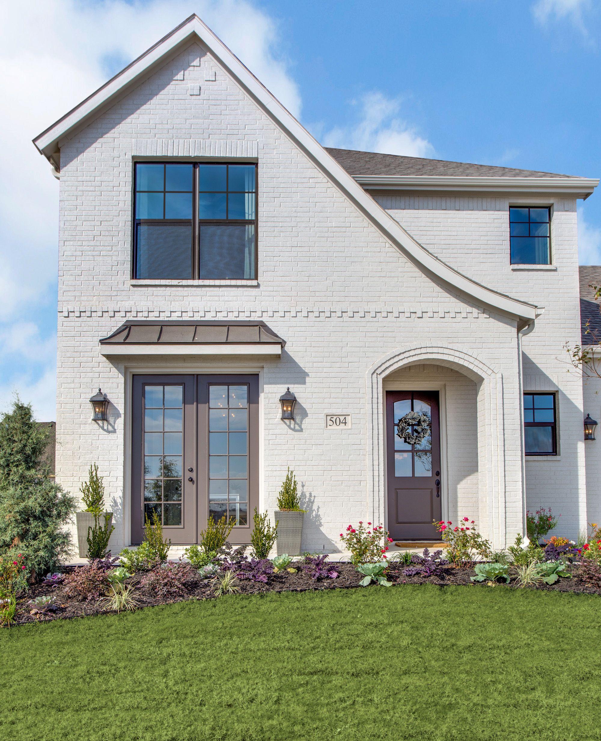 Tudor Home. White Painted Brick Tudor. Bronze Windows