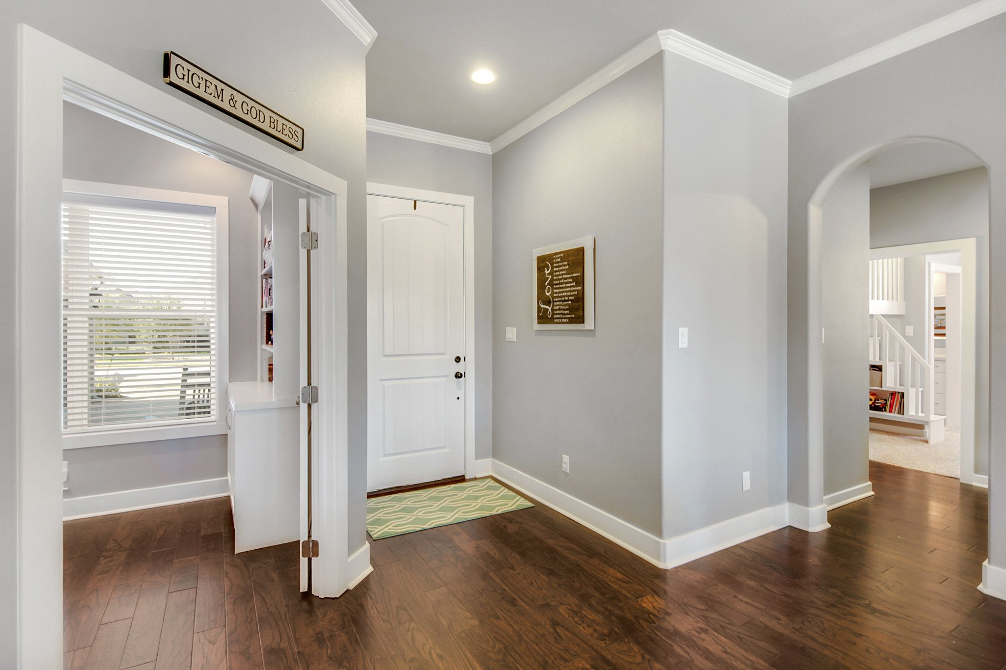 front entry with grey walls white crown molding dark wood floors