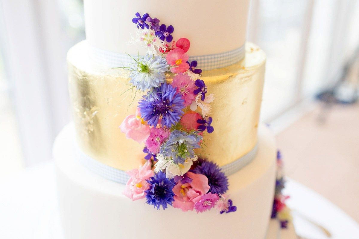 Gold and pink five tier wedding cake decorated with fresh flowers. Images by by laria Petrucci Photography