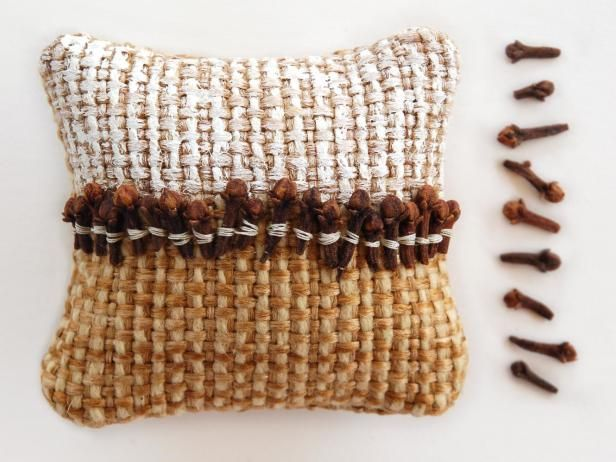 To create this pillow, begin with a rough, tan fabric for the base. Add a thin layer of white paint to the top half, letting your brush skim the surface of the fabric—you don't want paint in all the cracks. Add a row of cloves across the middle, stitching each on one at a time with white thread to create a thin stripe of white across the dark cloves.