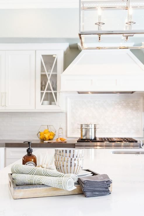 White french wood vent hood that graces this range has  classic high end presence over glass cooktop accent tiles cooktops also