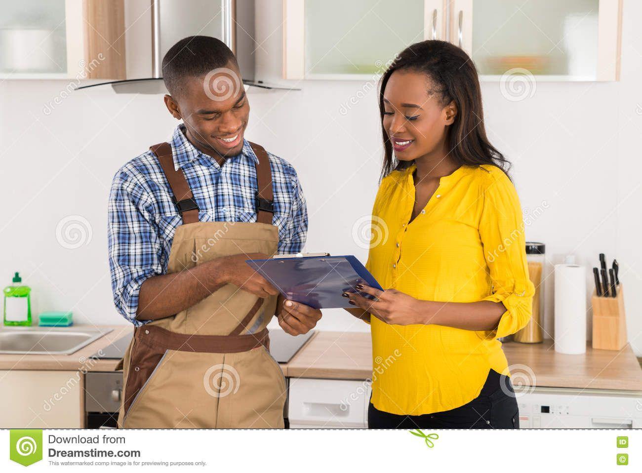 Handyman And Woman Looking At Clipboard Stock Image