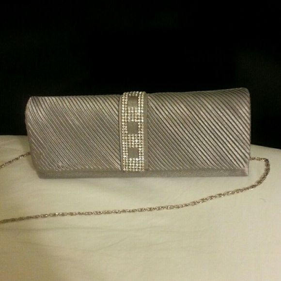 Over the Shoulder Purse/Clutch Silver colored clutch with rhinestones and over the shoulder chain. Used 1 time for prom. Slight smudge (shown in picture), but is covered when the clutch is closed and is only visible in direct light. Cleopatra Bags Clutches & Wristlets