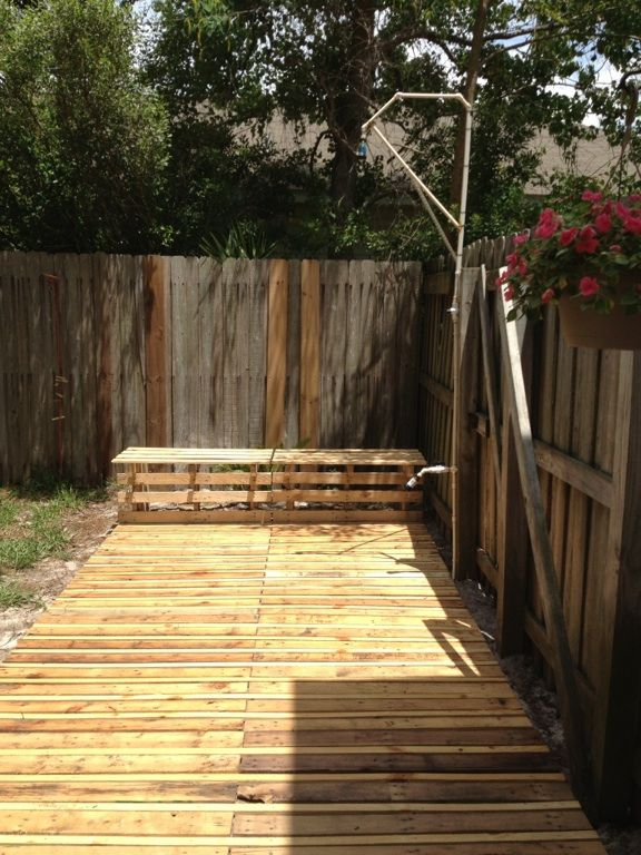 Outdoor shower with deck and seating made from pallets.