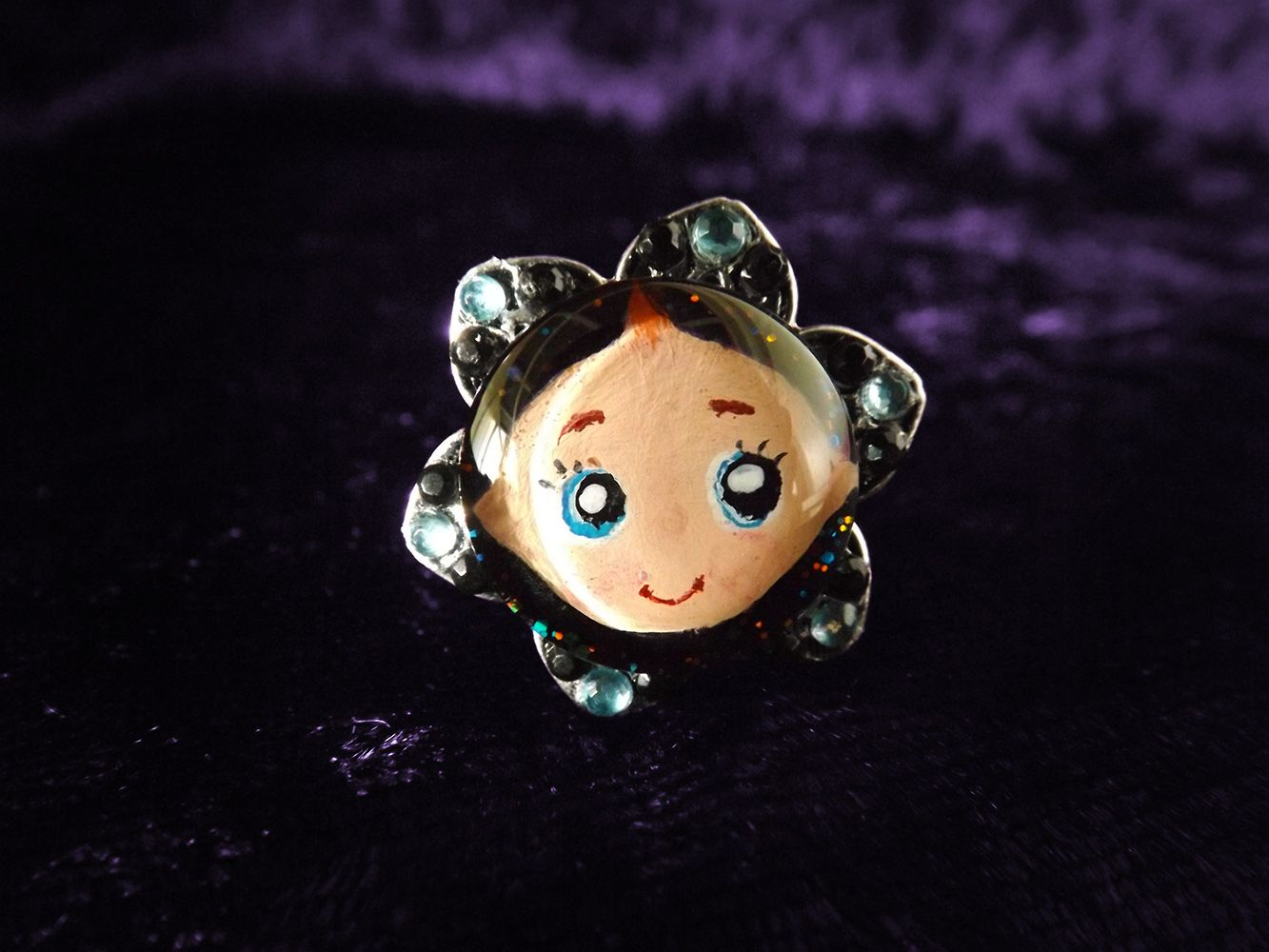 'Baby Ring' from Epheria - Bubby is here to bring you joy and heal your sads. Just look at that omnipotently adorable face, floating in the dark sparkly abyss. All hail Lord Bubby.  Hand-painted under a round 16mm glass domed cabochon, mounted on a size adjustable band, and adorned with baby blue and black diamantes.