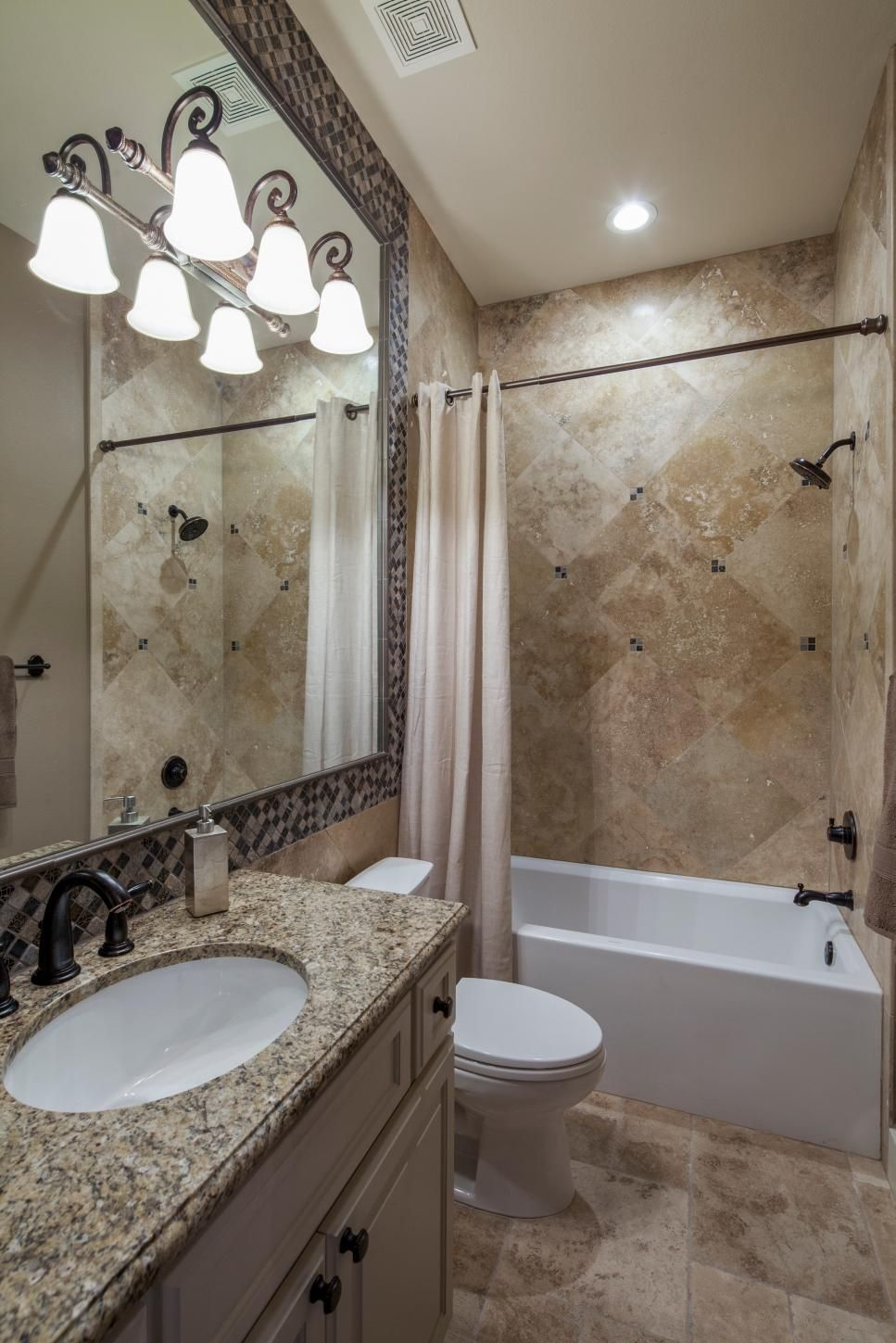 A sophisticated vanity a tile shower and mosaic tile detailing pack
