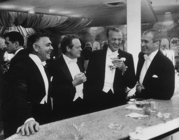 (left to right) Clark Gable, Van Heflin, Gary Cooper and James Stewart enjoy a joke at 1957 New Year's party held at the Crown Room in Romanoff's in Beverly Hills.
