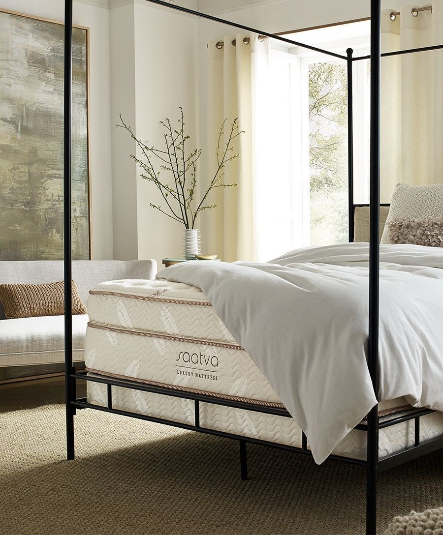 The Saatva Mattress On A Metal Frame In A Brightly Lit Room With