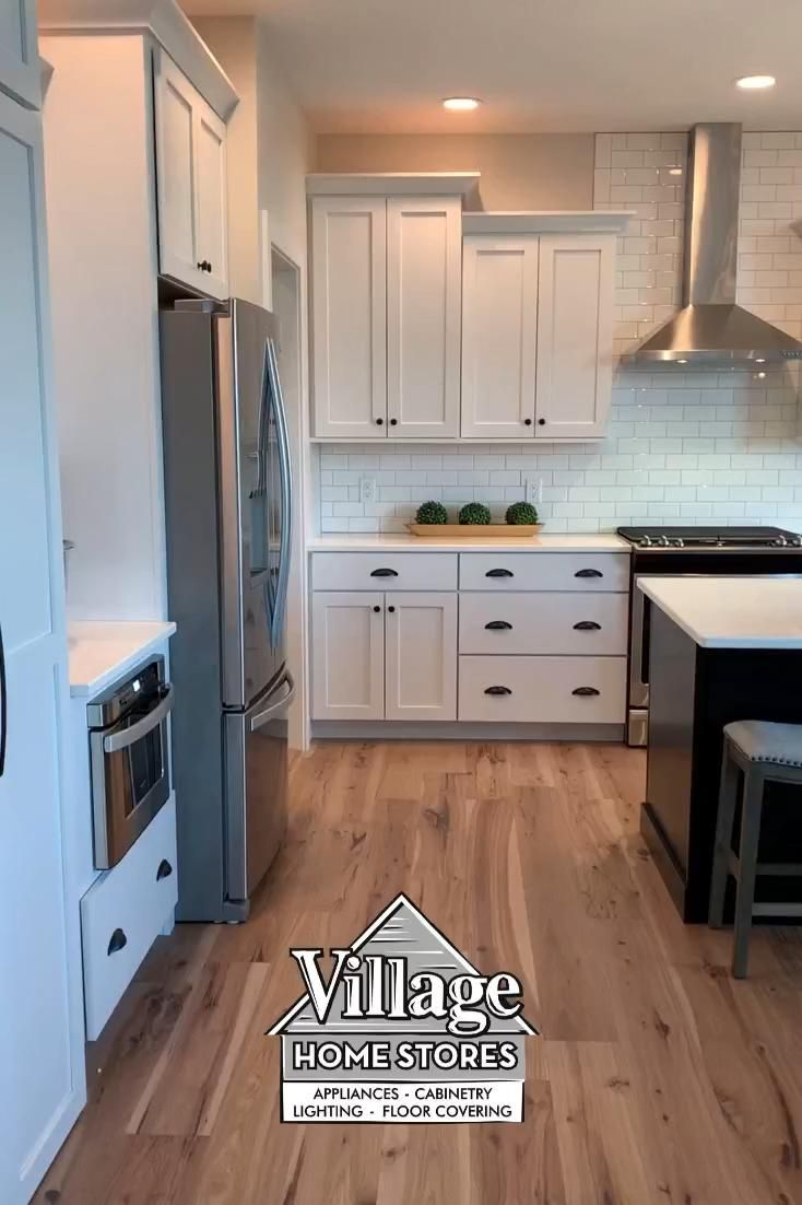 Modern #farmhouse #kitchen design with #matte black and white cabinets and Hanstone Strato quartz counters. Whirlpool appliances and Capital pendant #lighting also featured. Kitchen design by Village Home Stores for Aspen Homes of the Quad Cities.   |    villagehomestores.com