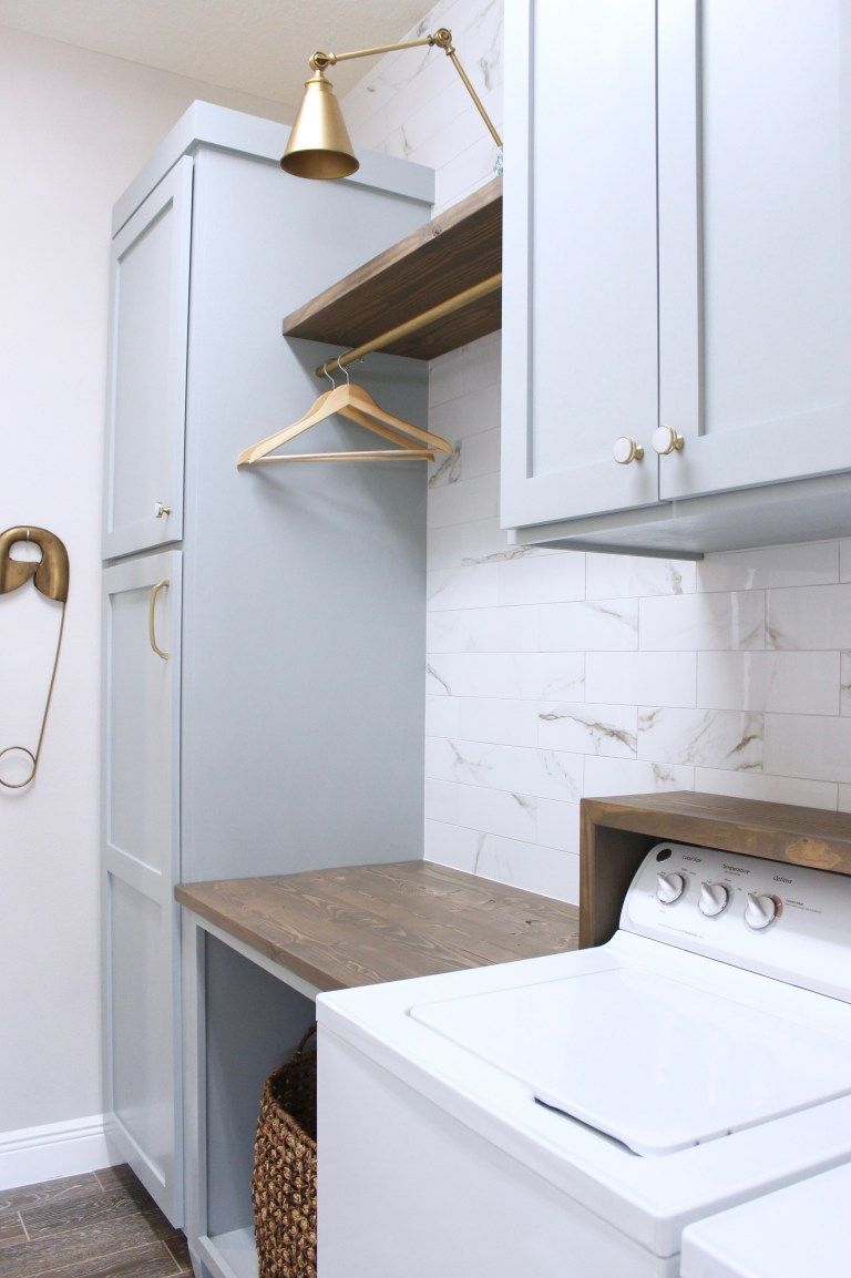 Photo of laundry room-diy-cabinets-painted-blue-marble-wall-tile-gold-sconce-light