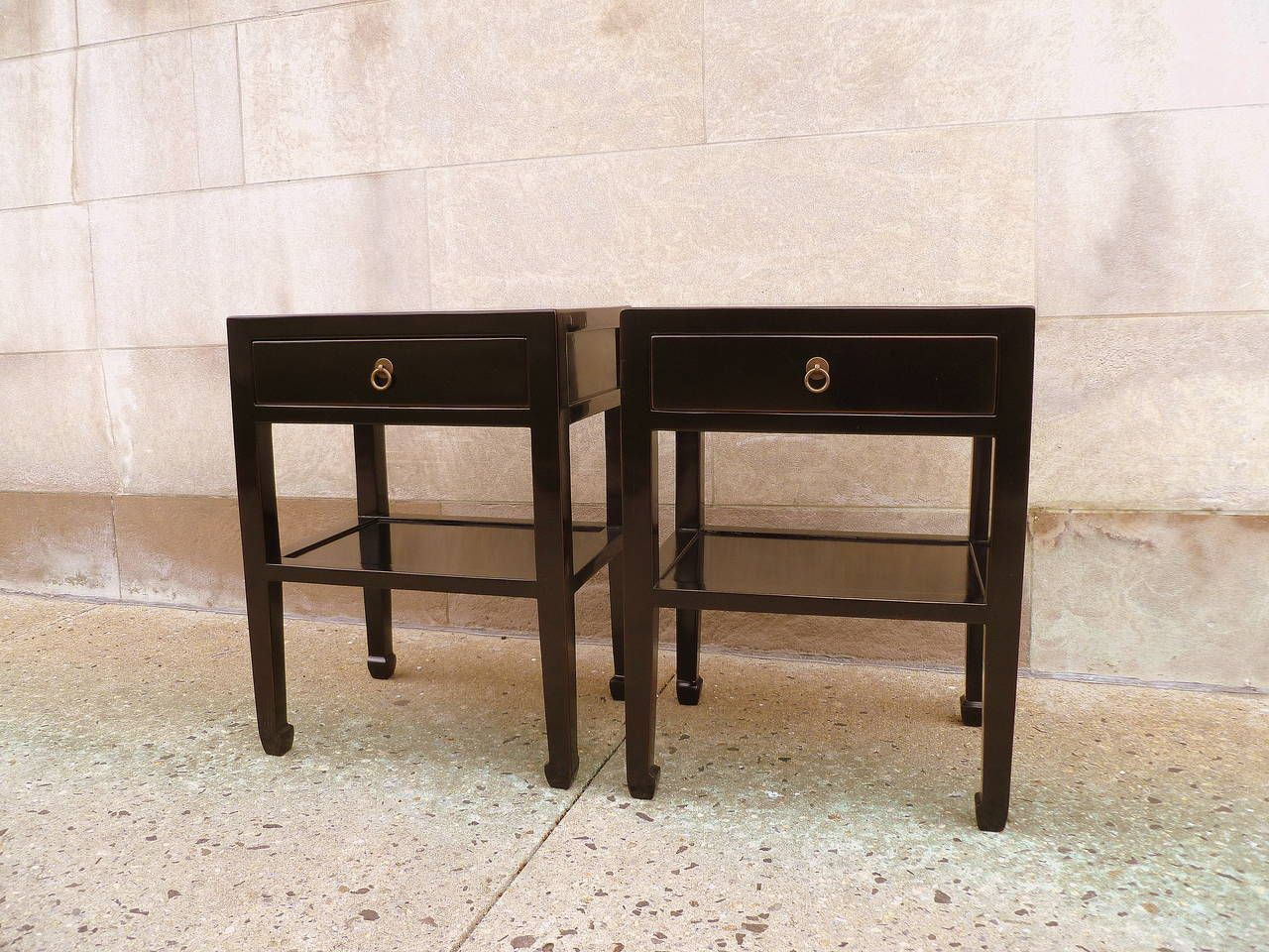 A pair of black lacquer end tables with shelf and drawer