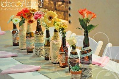 Centros de mesa en botellas de vidrio con flores mixtas.