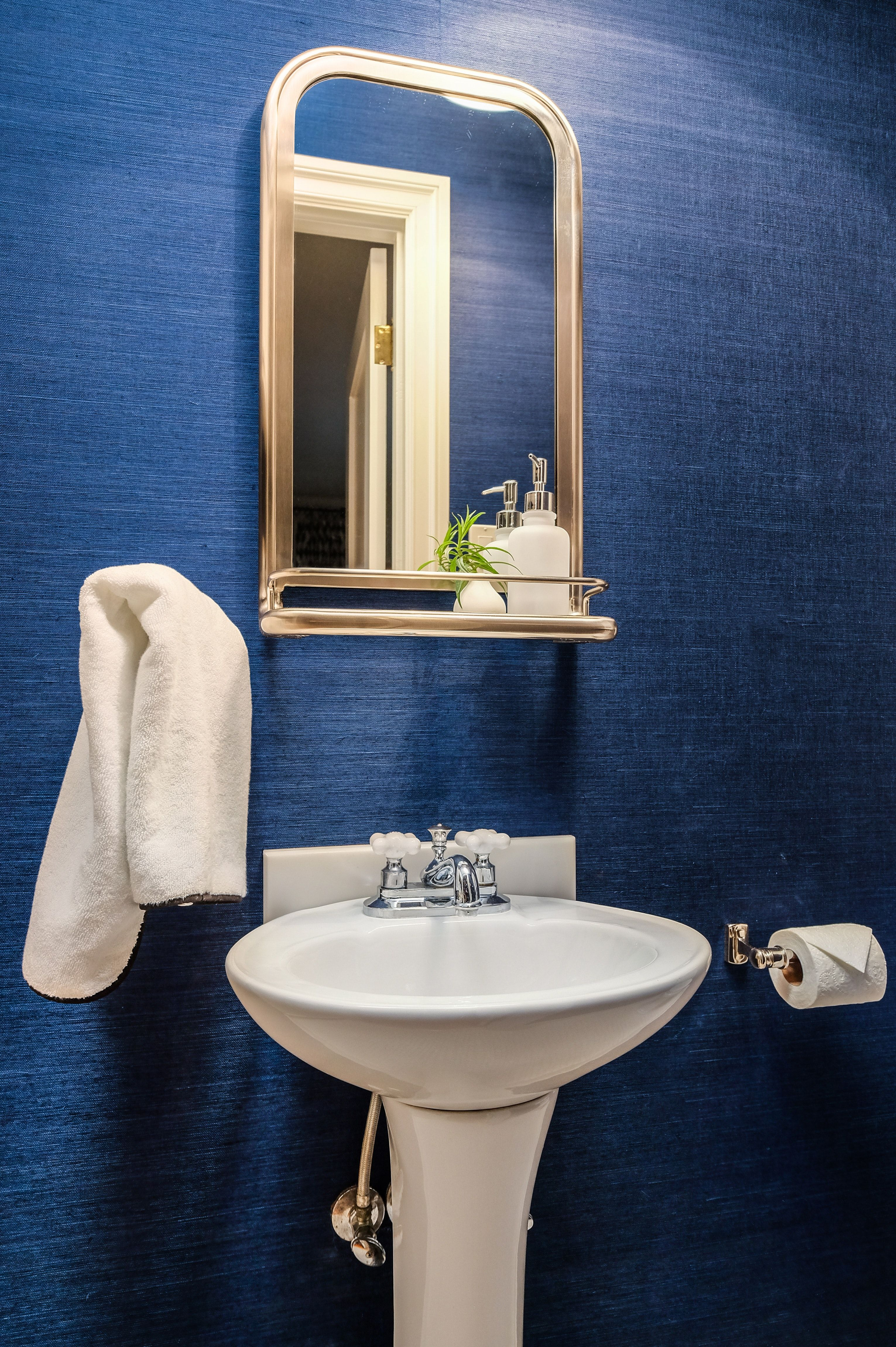Powder room with navy grasscloth wallpaper. Grasscloth
