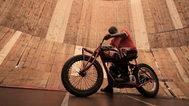 Jagath Perera - Steilwandfahrer auf der Wiesn in München. Motorräder: BMW Oldtimer und Indian Scout.