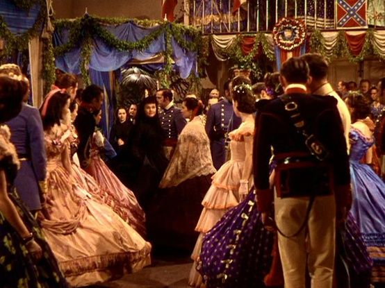 Scarlett: (tossing her head back) Oh, yes, I will! She throws open the trap of the booth defiantly, and - her black   dress in striking contrast as she walks through the blaze of colour, her head high, not looking at any of the shocked faces as the women draw their skirts away from her - she makes her way toward Rhett.