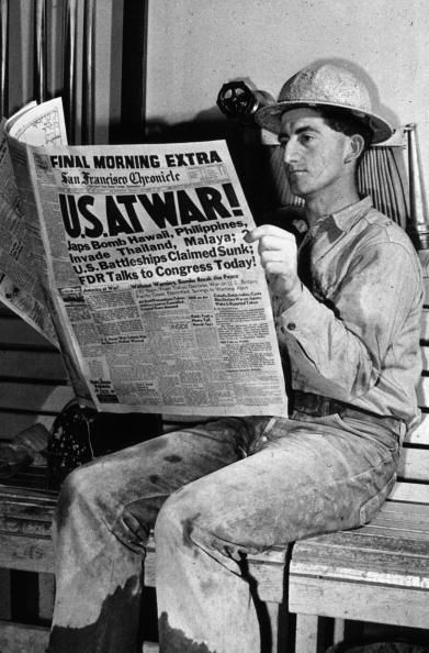 December 1941: A man reading an account of the bombing of Pearl Harbour (Pearl Harbor) in the San Francisco Chronicle at the Shasta Dam in California. (Photo by Russell Lee/Library Of Congress/Getty Images)