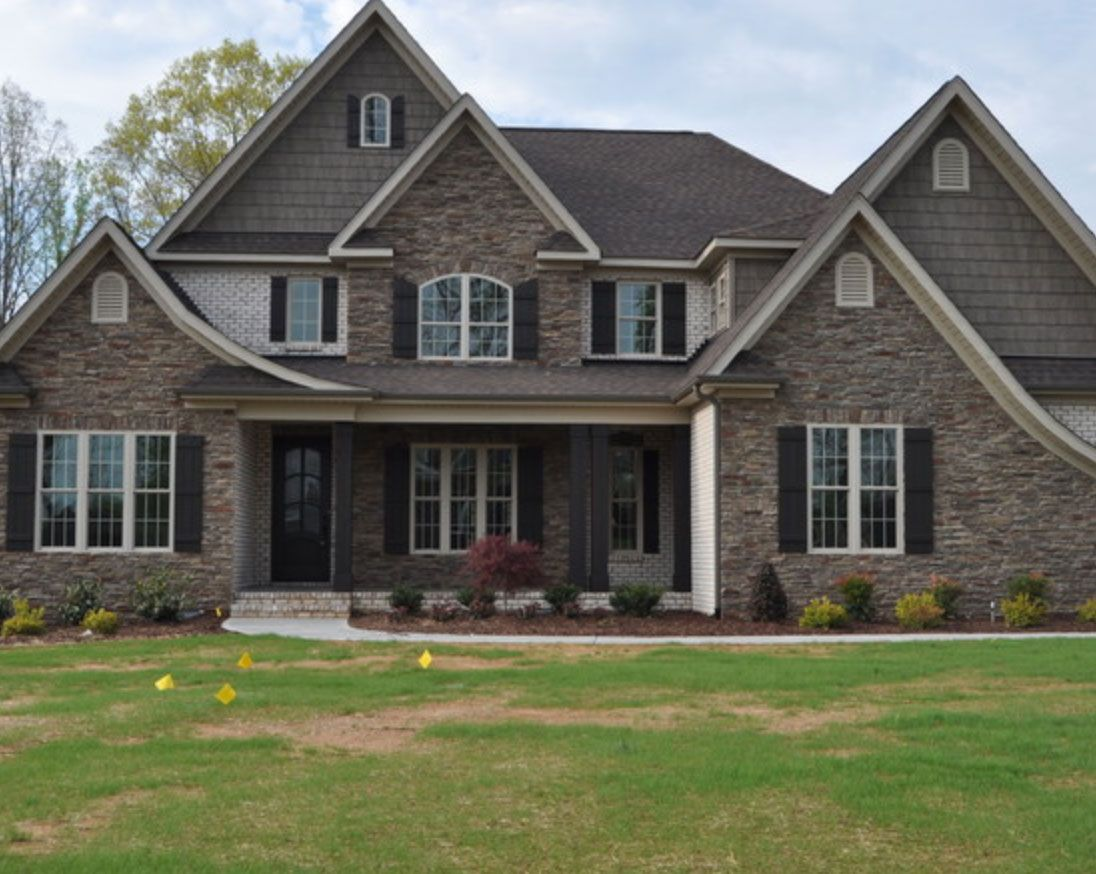 This stone home features sandy white chesapeake pearl for Stone and brick home designs