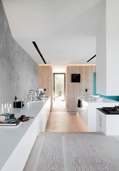 Clean long lines and sharp look in the kitchen. It is led into the living-room, where it acts as sideboard. At the back we see a box lined with Douglas-fir, which hides a coarse kitchen with fridge and freezer.