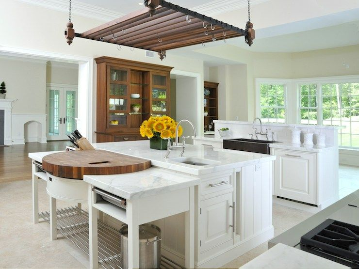 Beautiful kitchen features pot rack suspended from ceiling over white kitchen island topped with white marble accented with prep sink and paired with gooseneck faucet situated next to prep island with round butcher block top flanked by pull-out drawers atop cream tiled floor across from second kitchen island with raised breakfast bar framed with apron sink.