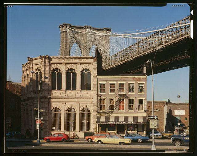 VIEW OF BROOKLYN TOWER EMERGING BEHIND NINETEENTH CENTURY COMMERCIAL BUILDINGS ON THE CORNER OF FRONT STREET AND CAMDEN PLAZA - Brooklyn Bridge, Spanning East River between Park Row, Manhattan and Sands Street, Brooklyn, New York, New York County, NY